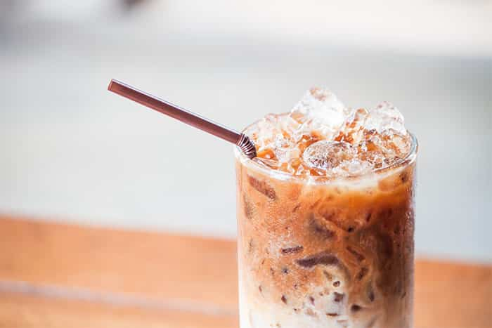 Glass of cold coffee latte with ice cubes up close